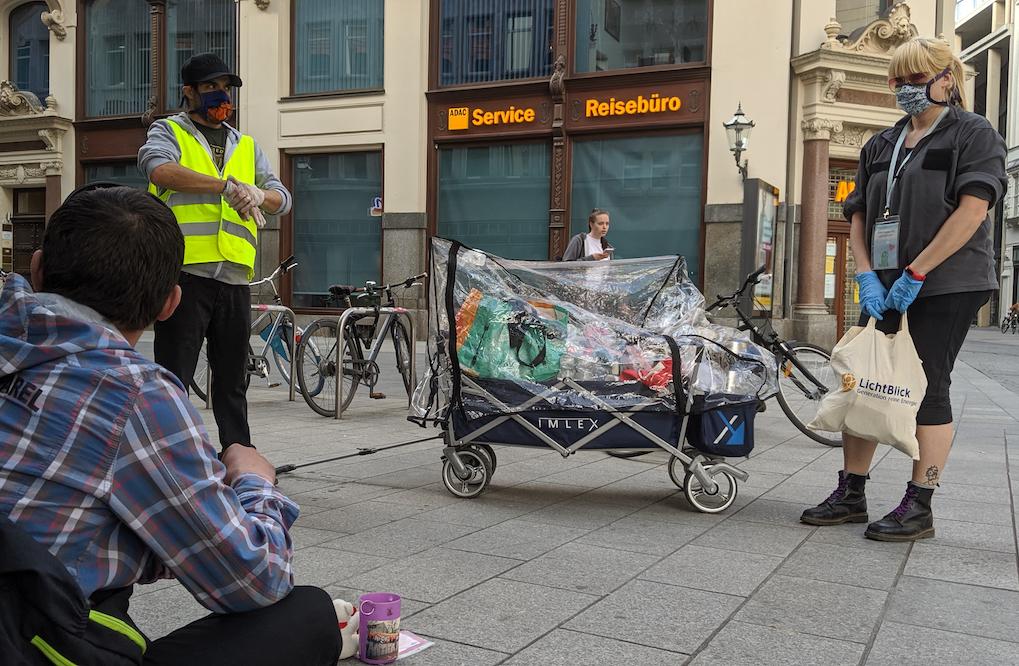 Zwei Menschen und ein Bollerwagen stehen vor einem Obdachlosen