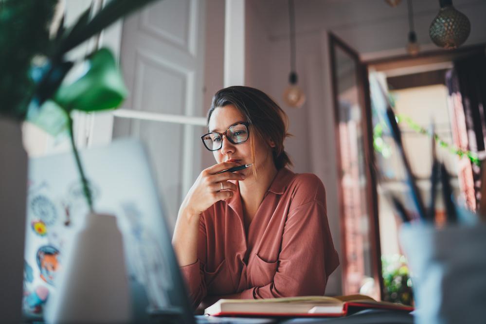Eine Frau mit Brille sitzt vor einem Laptop