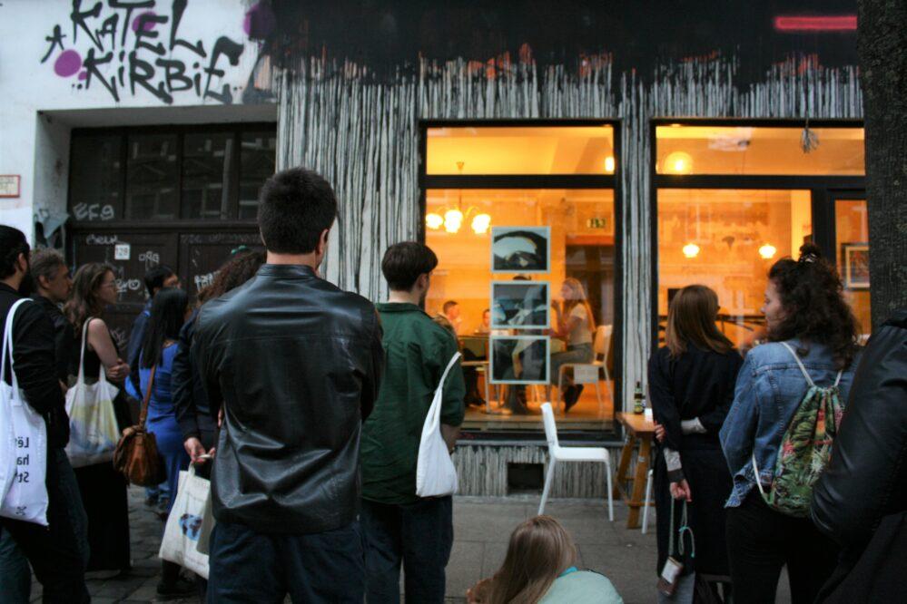 Menschen stehen vor einem beleuchteten Schaufenster in dem Fotos hängen