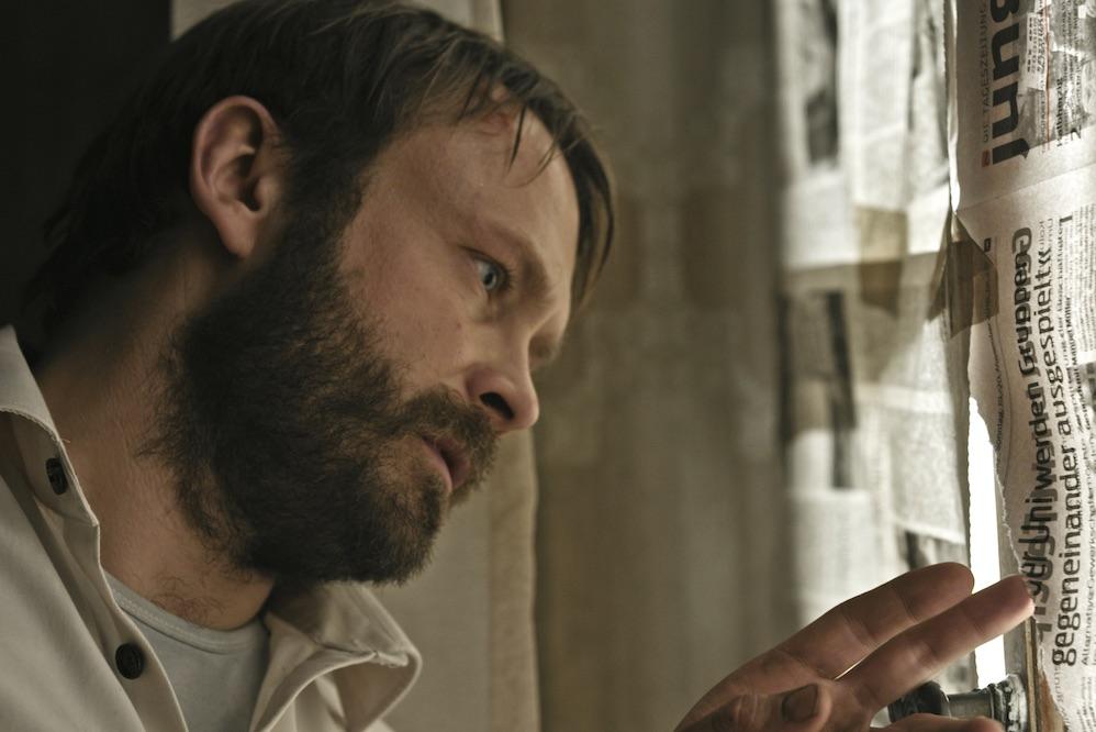 Ein Mann mit Bart und weißem Hemd linst durch ein mit Zeitungspapier abgeklebtes Fenster