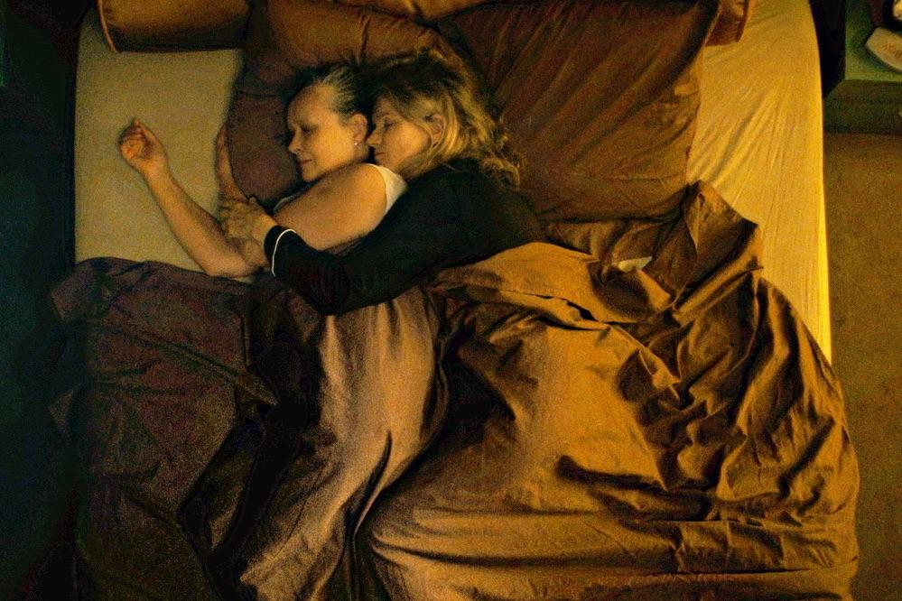 Zwei Frauen liegen aneinandegekuschelt im Bett