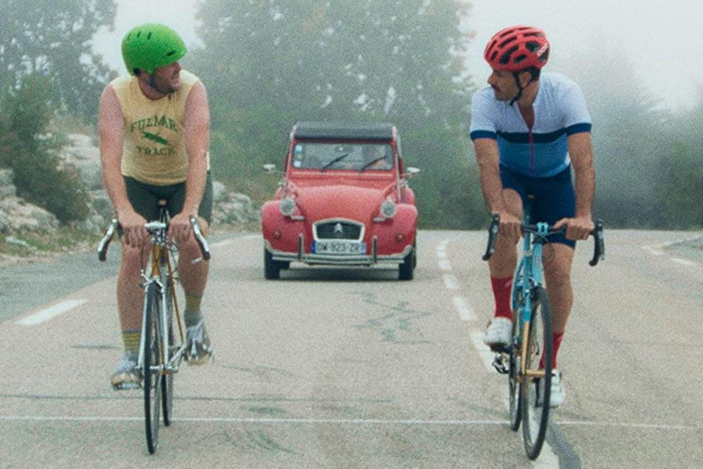 Zwei Männer auf Rennrädern fahren vor einem roten Auto