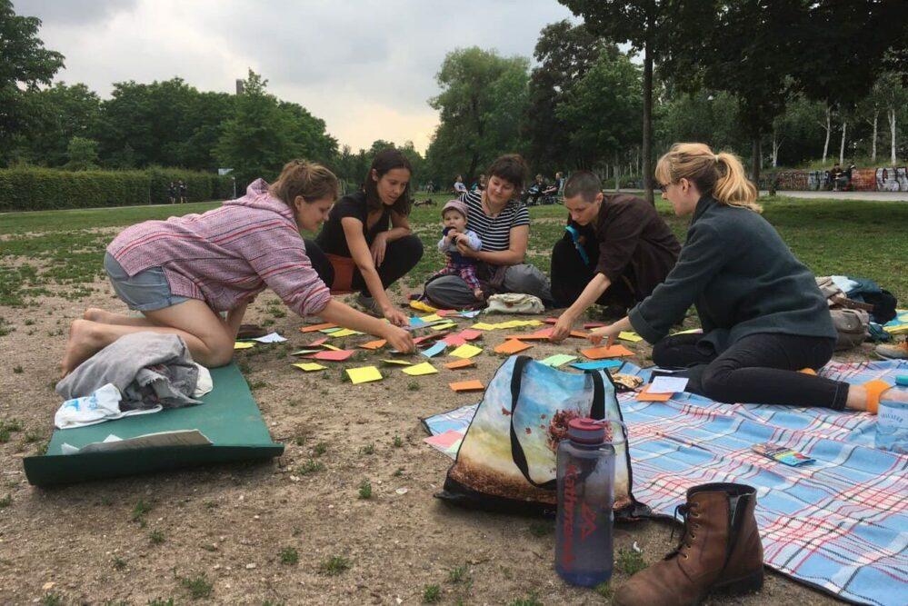 Menschen sitzen auf dem Boden um Zettel verteilt